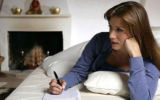 Thoughtful brunette woman lying with a notepad on the sofa